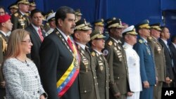 Photo provided by the Miraflores Presidential Palace shows President Nicolas Maduro, second from left, and first lady Cilia Flores during a event marking the 81th anniversary of the National Guard, in Caracas, Venezuela, Aug. 4, 2018.