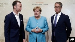 From left, Handelsblatt chief editor Sven Afhueppe, German Chancellor Angela Merkel and the Handelsblatt publisher Gabor Steingart pose for a photo prior to the 'Deutschland Live' event organized by the economy news paper 'Handelsblatt' in Berlin, Aug. 23, 2017.