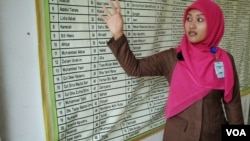 Salmi Hardiyanti, now 24, points to the names of nine of her relatives who died in the tsunami. Their bodies have never been found. (Steve Herman/VOA News)