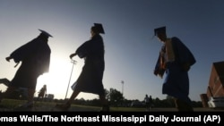 In this June 27, 2020, file photo, Saltillo High School seniors make their way to the football field as the sun begins to set for their graduation ceremony in Saltillo, Mississippi.