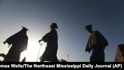 In this June 27, 2020, file photo, Saltillo High School seniors make their way to the football field as the sun begins to set for their graduation ceremony in Saltillo, Mississippi. (Thomas Wells/The Northeast Mississippi Daily Journal via AP, File)
