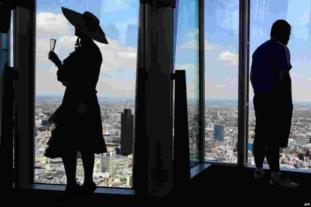 "A member of the Chap Olympiad group known as ""Auntie Maureen"" (L) poses for photographs at the press launch of London's highest lawn in the Shard building, Britain."
