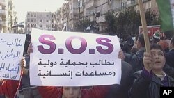 """3月2日在霍姆斯,抗議者舉著橫幅,上面寫著""""要求國際保護和人道援助""""字樣的標語牌。"""