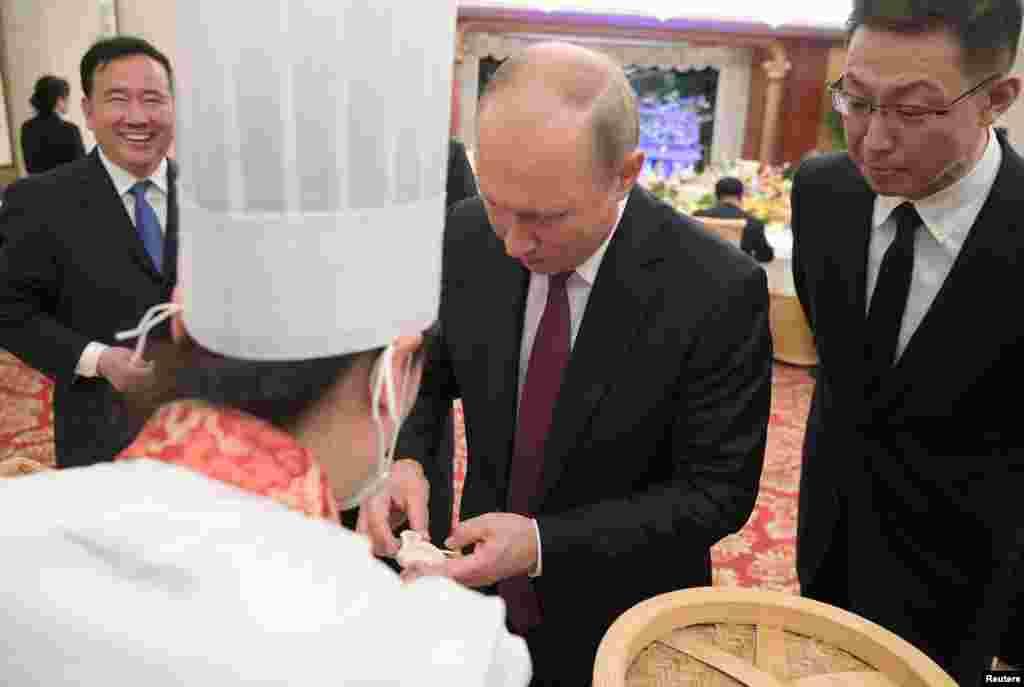 俄罗斯总统弗拉基米尔·普京2018年6月8日在中国天津参加招待会,学习做包子。