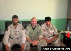 In this undated photo provided by Ryan Brummond, U.S. Special Forces Officer Ryan Brummond, center, is seated next to Mohammad Khalid Wardak, right, in Afghanistan.