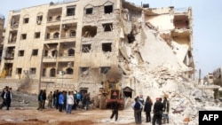 Syrians gather next to the scene of an explosion in Aleppo, January 18, 2013.