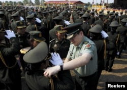 A Chinese army advisor (C) puts rank on Cambodian army graduates during a graduation ceremony at Army Institute in Kampong Speu province March 12, 2015.