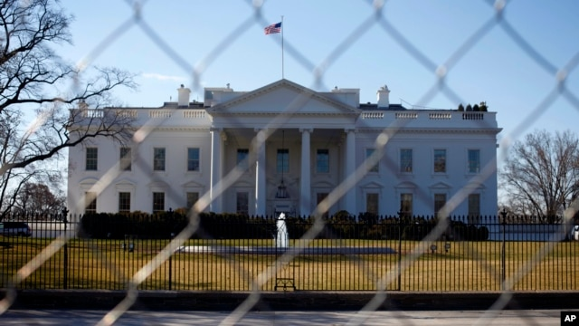 In this March 4, 2013, photo, The White House is seen through a chain-link fence where the inaugural reviewing stand once stood in Washington.
