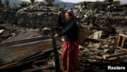 An earthquake victim cuts wood from the debris of her house in Barpak village, the epicenter of the April 25 earthquake in Nepal.