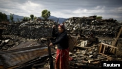 Seorang korban gempa bumi menotong kayu dari reruntuhan rumahnya di desa Barpak, pusat gempa bumi tanggal 25 April di Nepal.