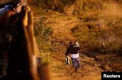 Migrant iz Hondurasa, dio karavana hiljada migranata iz Centralne Amerike koji pokušavaju da se domognu SAD, trči sa svojim sinom nakon što je ilegalno prešao iz Meksika u Ameriku tako što je preskočio graničnu žicu, na graničnom zidu pored Tijuane, Meksiko, 13. januara 2019.
