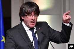 FILE - Ousted Catalan leader Carles Puigdemont addresses Catalan mayors who traveled to Brussels in support of the ousted Catalan government in Brussels, Belgium, Nov. 7, 2017.