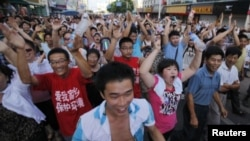 ປະຊາຊົນໃນທ້ອງຖິ່ນ ເດີນຂະບວນປະທ້ວງ ຕໍ່ແຜນການວາງທໍ່ນໍ້າເສຍ ຈາການຜະລິດອຸດສາຫະກໍາ ຢູ່ໃນເຂດ Qidong, ປະເທດຈີນ, ໃນວັນເສົາ ທີ 28 ກໍລະກົດ, 2012.