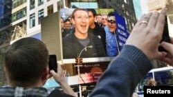 CEO Facebook, Mark Zuckerberg (tampak pada layar TV) menandai dimulainya perdagangan perdana (IPO) di bursa NASDAQ New York dengan dering bel jarak jauh dari Menlo Park, California (18/5).