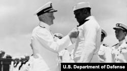 Адмирал ВМС США Честер Нимиц (в честь которого тоже назван авианосец) награждает орденом матроса Дориса Миллера, 27 мая 1942 г.