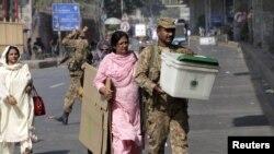 ایک فوجی اہلکار انتخابی عملے کے ساتھ سامان پولنگ اسٹیشن کی جانب لے جارہا ہے (فائل فوٹو)