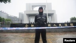 A police officer stands outside the Hefei Intermediate People's Court, where Gu Kailai is being tried for murder, in Hefei, Anhui Province August 9, 2012.