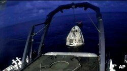 In this image taken from SpaceX video, a SpaceX capsule carrying four people is lifted from the Atlantic Ocean off the Florida coast onto a recovery vessel, Sept. 18, 2021.
