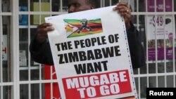 """Um homem com um cartaz que diz """"O povo quer que Mugabe saia"""" Nov. 18, 2017."""