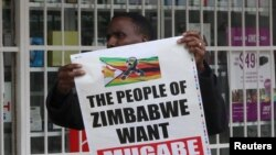 A man carries a poster calling for Zimbabwe President Robert Mugabe to step down as Zimbabweans take to the streets in Harare, Zimbabwe, Nov. 18, 2017.