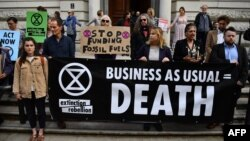 Climate change activists stage a protest outside the H M Treasury building in central London, April 25, 2019, during environmental protests by the Extinction Rebellion group.
