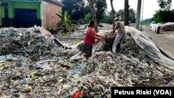 Supiati dan Saji mengangkut sampah plastik impor di pekarangan mereka, di Desa Bangun, Kecamatan Pungging, Kabupaten Mojokerto, untuk kemudian disortir dan dijual kembali. (Foto: Petrus Riski/VOA)