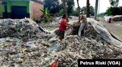 Supiati dan Saji mengangkut sampah plastik impor di pekarangan mereka, di Desa Bangun, Kecamatan Pungging, Kabupaten Mojokerto, untuk kemudian disortir dan dijual kembali, Juni 2019. (Foto: Petrus Riski/VOA)