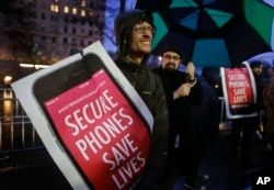 FILE - Protesters demonstrate against a government demand that Apple unlock an iPhone at a rally outside the Apple store on Fifth Avenue in New York, Feb. 23, 2016.