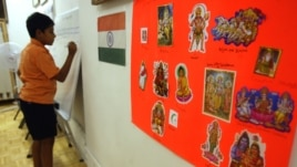A poster displaying the religions of India and the Indian flag hang on the wall at the India Heritage Camp in 2006. A new study shows Hindus are more educated and earn more than any other religion in the U.S.