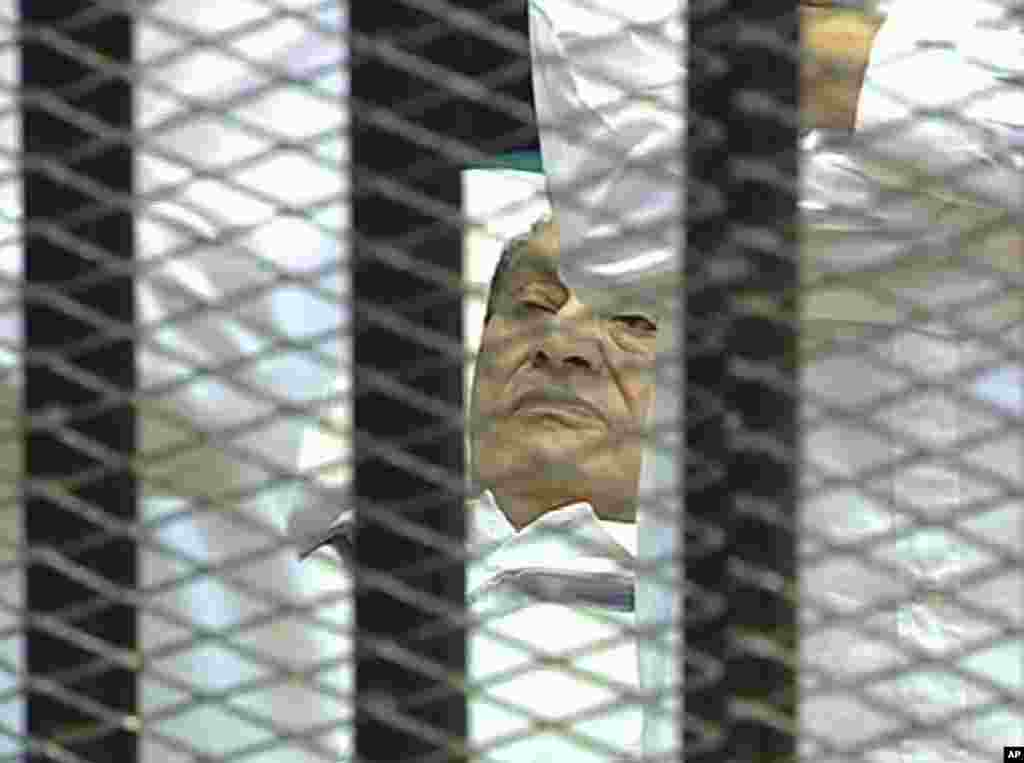 Video image taken from Egyptian State Television showing former President Hosni Mubarak, 83, laying on a hospital bed inside a cage in a Cairo courtroom as his historic trial began on charges of corruption and ordering the killing of protesters during the