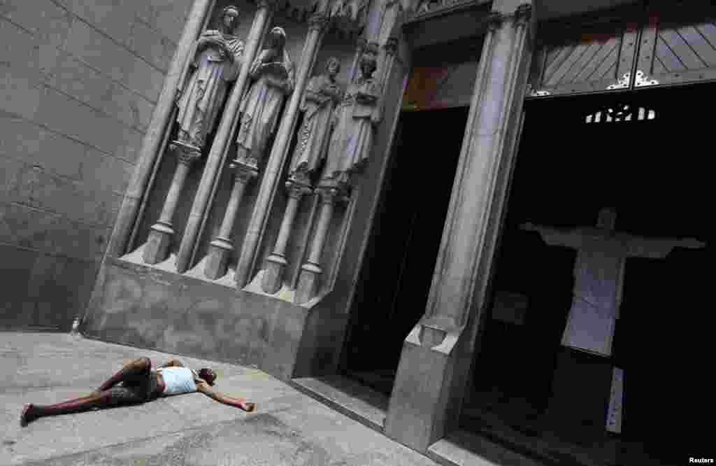 Beskućnik u dubokom snu ispred ulaza u katedralu Sao Paulo u Sao Paulu, Brazil.