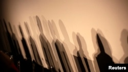 "FILE - Shadows of members of a panel appear on a wall before a meeting about the ""right to be forgotten"" in Madrid, Sept. 9, 2014."