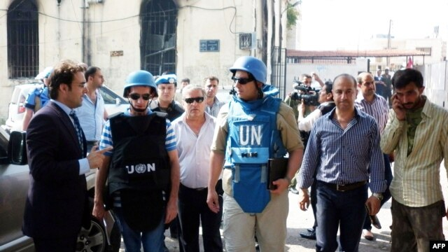 A team of United Nations observers tours the Syrian town of al-Haffe with an official Syrian security escort, June 14, 2012.