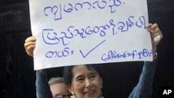 "Myanmar's pro-democracy leader Aung San Suu Kyi displays a placard that reads, ""I also love the people,"" to her supporters at the headquarters of her National League for Democracy Party in Yangon, Burma, 14 November 2010"