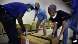 From left, Tim Williams, warehouse assistant for Medisys, Ray Fredericks, assistant director for Medisys, and Dr. Abhu Kaur with Khalsa Aid USA load supply to be shipped to New Delhi May 7, 2021. (AP Photo/Jessie Wardarski)