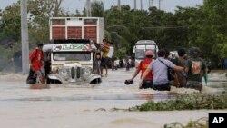 Warga wilayah San Ildefonso, propinsi Bulacan, Filipina terpaksa harus melewati jalanan yang tergenang banjir akibat hantaman Topan Nari, Sabtu (12/10).