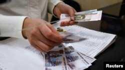A cashier counts a pension payment in Russian roubles, in a post office at the Crimean city of Simferopol, March 25, 2014.