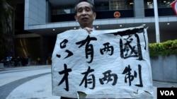 支持港獨的梁先生手持示威牌突破保安人員阻攔進入公民廣場。(美國之音湯惠芸)