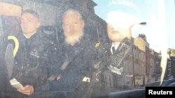 Pendiri WikiLeaks Julian Assange (tengah) di dalam mobil van polisi, meninggalkan pengadilan di London, Inggris, Kamis (11/4).