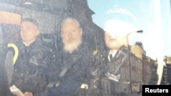 WikiLeaks founder Julian Assange (C) leaves the Westminster Magistrates Court in a police van, after he was arrested in London, Britain, April 11, 2019.