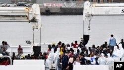 """Activistas sostienen una pancarta que dice """"Detengan el ataque a los refugiados"""" mientras los inmigrantes aguardan para desembarcar del buque """"Disciotti"""" de la Guardia Costera italiana, en el puerto siciliano de Catania, en el sur de Italia, el miércoles 13 de junio de 2018."""