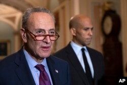 Senate Minority Leader Chuck Schumer, D-New York, with Sen. Cory Booker, D-New Jersey, at right, pauses as they speak to reporters about the political battle around the confirmation of President Donald Trump's Supreme Court nominee, Brett Kavanaugh, on Capitol Hill in Washington, Oct. 2, 2018.