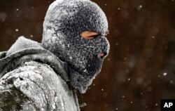 Alec Bender is covered with snow while he and some friends were sledding, Jan. 28, 2014, in Knoxville, Tennessee.