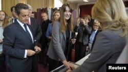 Mantan ibu negara Perancis, Carla Bruny-Sarkozy, memasukkan surat suaranya ke kotak penitipan suara di salah satu TPS di Paris (10/6).