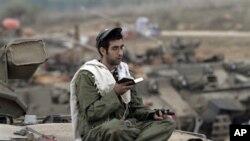 Seorang tentara Israel tengah berdoa sambil berjaga di perbatasan dekat Gaza, selatan Israel (22/11). (AP/Lefteris Pitarakis)