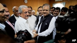 Mamnoon Hussain, center right, a presidential candidate from ruling party Pakistan Muslim League-N shakes hands with Raza Rabbani, a candidate from opposition party Pakistan People Party in Islamabad, July 24, 2013.