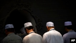 FILE - Chinese Hui Muslims pray during Eid al-Fitr prayers at Niujie Mosque in Beijing, July 18, 2015. Authorities in northwestern China were poised to begin demolition of a mosque Friday, despite protests by hundreds of members of the country's Muslim Hui ethnic minority determined to preserve the newly built structure.