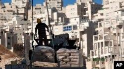 ARSIP – Seorang pekreja berdiri di samping material konstruksi yang akan dibongkar di unit perumahan baru di lingkungan Har Homa (2/11/2011). Yerusalem Timur, Israel. (foto: AP Photo/Sebastian Scheiner)