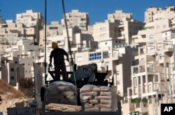 FILE - A worker stands by construction materials to unload at a new housing unit in the east Jerusalem neighborhood of Har Homa, Nov. 2, 2011.