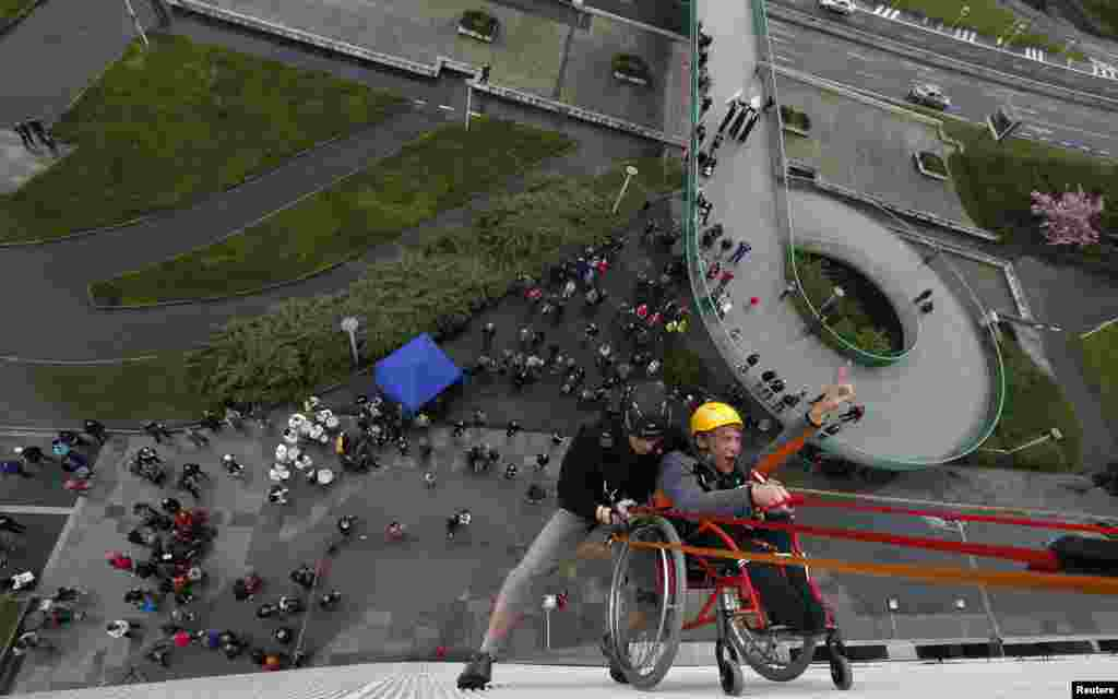Jakub Koucky (R), a graduate from Jedlickuv Institute, in a wheelchair, is helped by a climber during the first ever attempt to rappel from Prague's Congress Center at an event to mark the institute's 100th founding anniversary in Prague, Czech Republic.